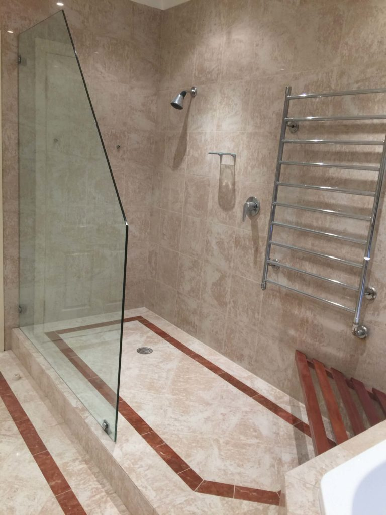 Travertine tile shower leaking due to membrane failure, photos show moisture damage, cracked wall and floor grouts. 1/14