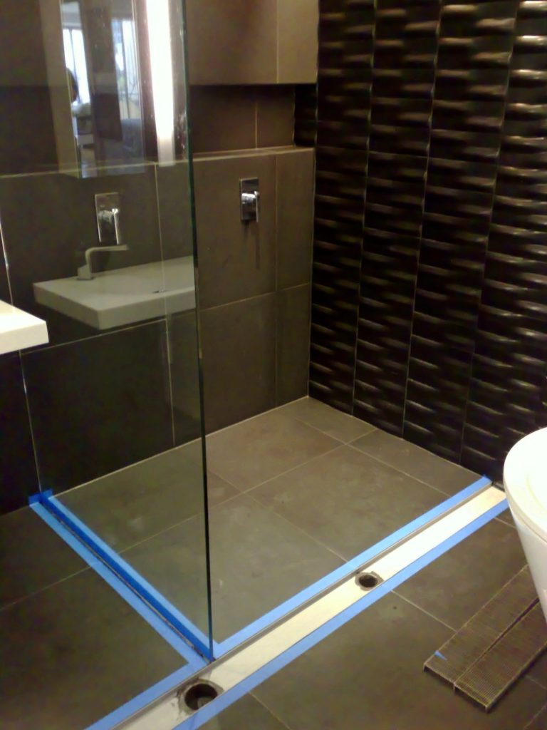 Bluestone floor area with liner grate and pressed metal wall sheeting.